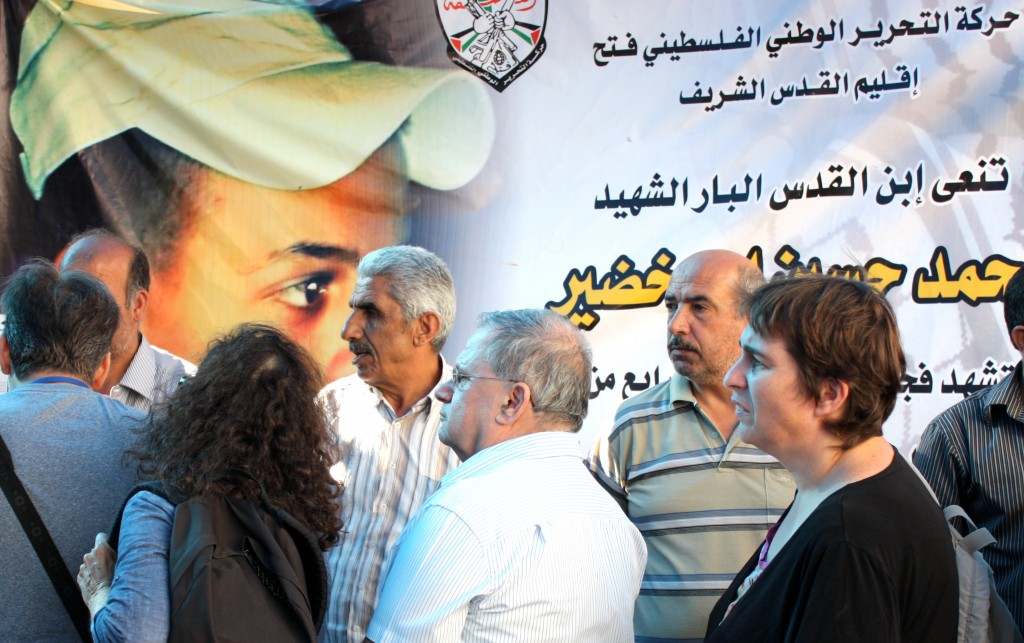 "Members of the family of Muhammad Abu-Khdeir receive Israeli visitors who came to share in their grief in the Palestinian neighborhood of Shuafat in Jerusalem. The poster in the background reads: ""The Palestinian National Liberation Movement, Fatah, Jerusalem area, mourns for the righteous son of Jerusalem, Muhammad Abu Khdeir, murdered as a martyr..."""